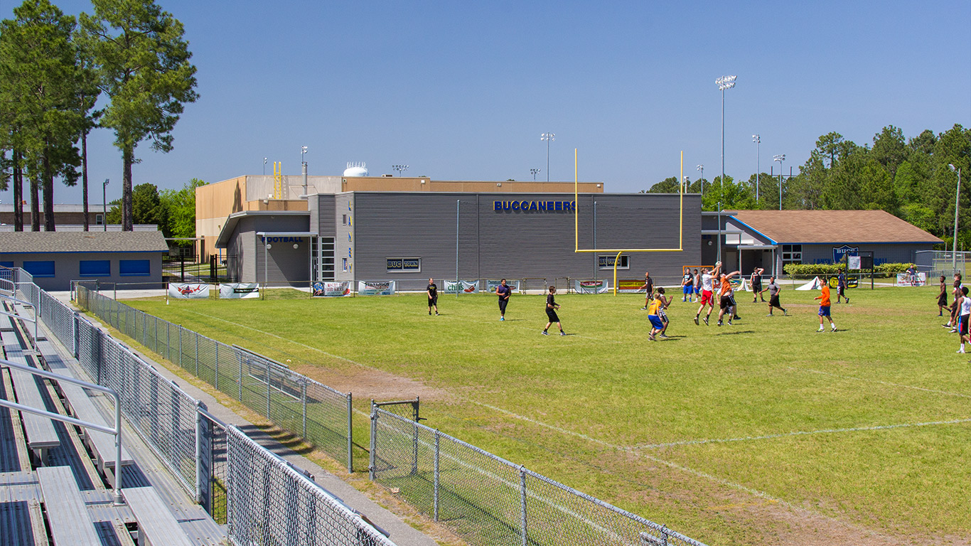 Children play on the football field at the E.A. Laney High School Media Center & Gymnasium
