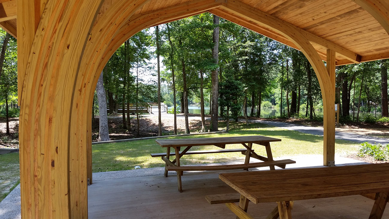 Inside a pavilion at Millers Pond Park looking toward a lake